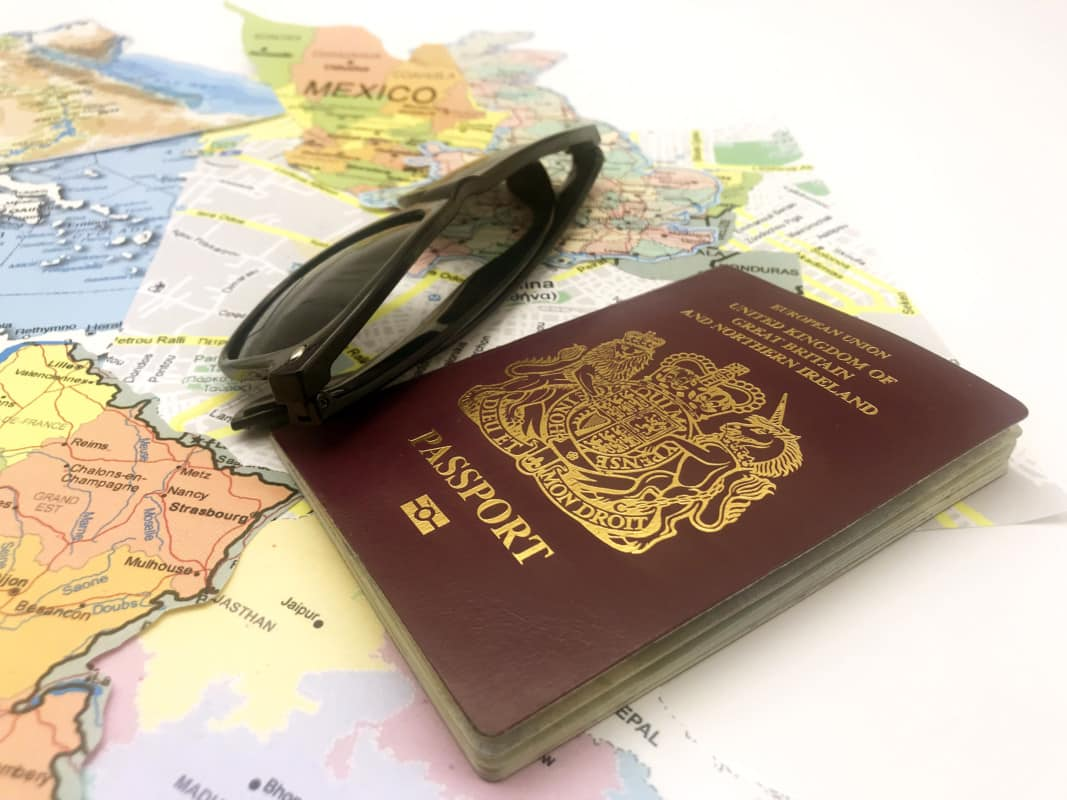 """A passport and sunglasses on a map"""