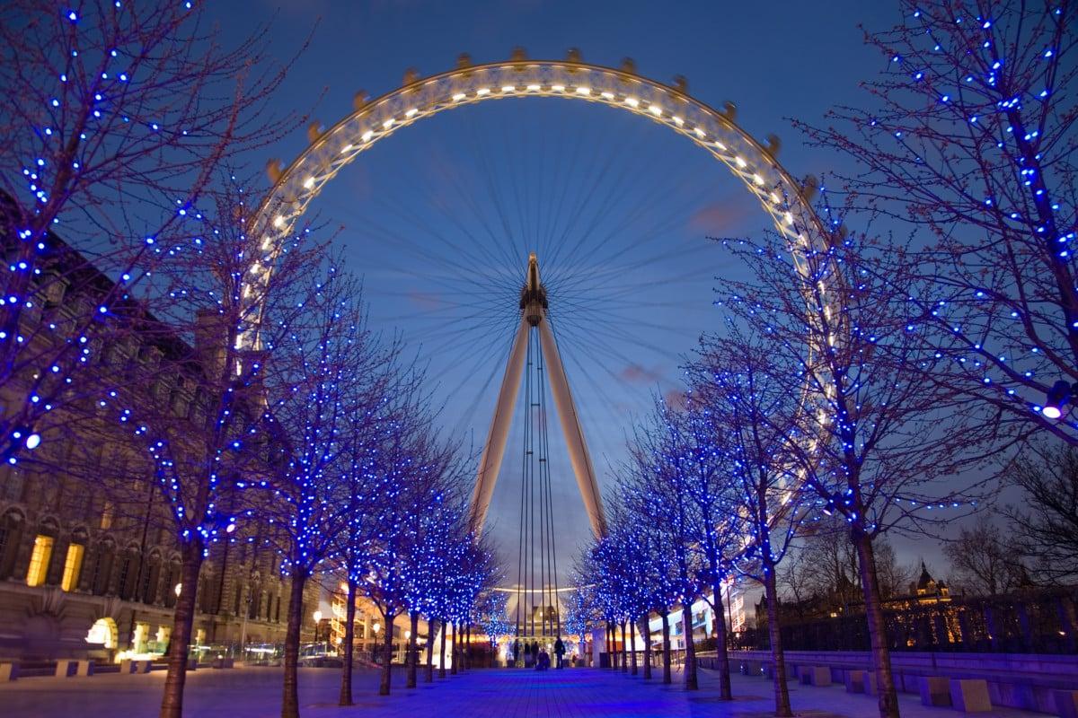 """The London Eye illuminated at twilight with trees around"""